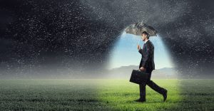 Young businessman with umbrella under rain walking on field