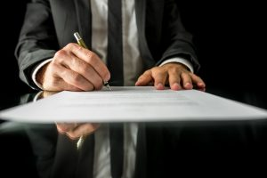 Front view of businessman signing important legal document on black desk with reflection.
